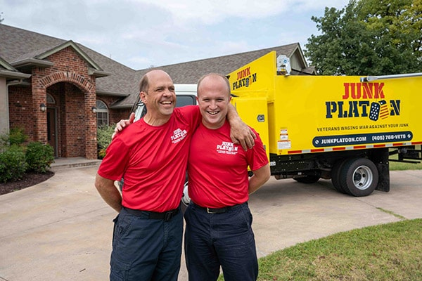 Junk removal professionals standing in front of their truck